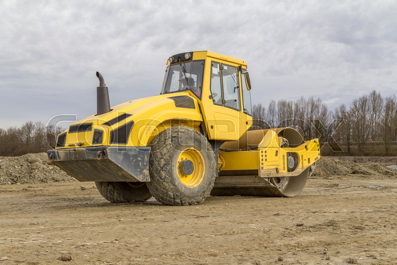 Yellow road roller at a loamy construction site, stock photo