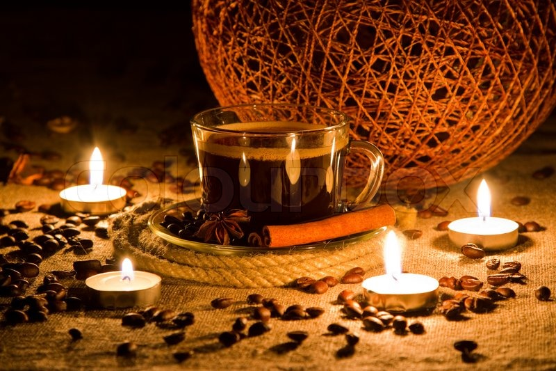 Cup of coffee in natural candle lighting, stock photo