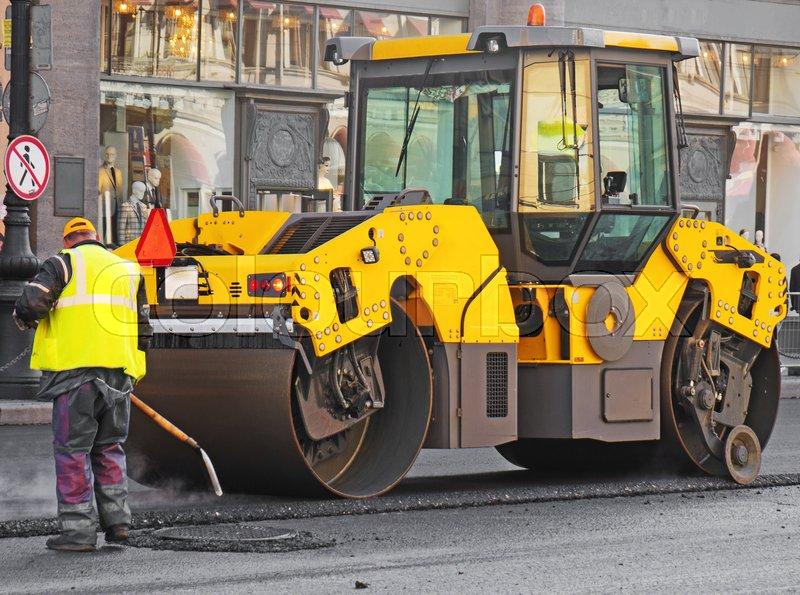 Road re-construction. Road roller stacking hot asphalt, stock photo