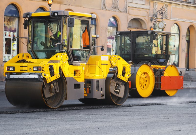 Road re-construction. Road rollers stacking hot asphalt, stock photo