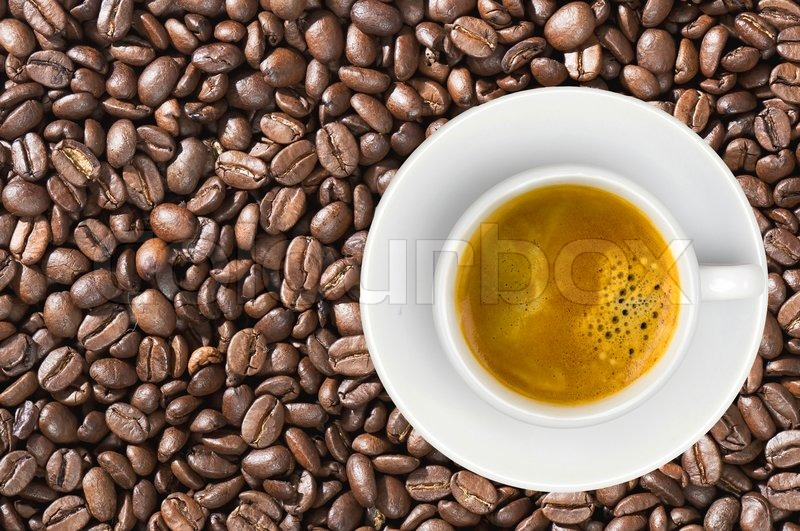 White cup of coffee espresso over coffee beans background, stock photo