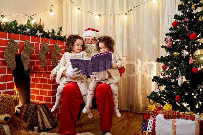 Santa Claus with children twin girls on his lap chiteyut book at Christmas, New Year in the room by the fireplace and Christmas tree. The concept of Merry Christmas, New Year, stock photo