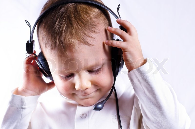Stock image of 'The serious little boy in ear-phones with a microphone in call center answers a call on a white background'