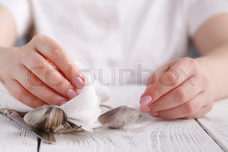 Female hand cleaning spotty silverware with a cleaning product and a cloth,Close up woman hand cleaning silver spoon,polished silver, stock photo
