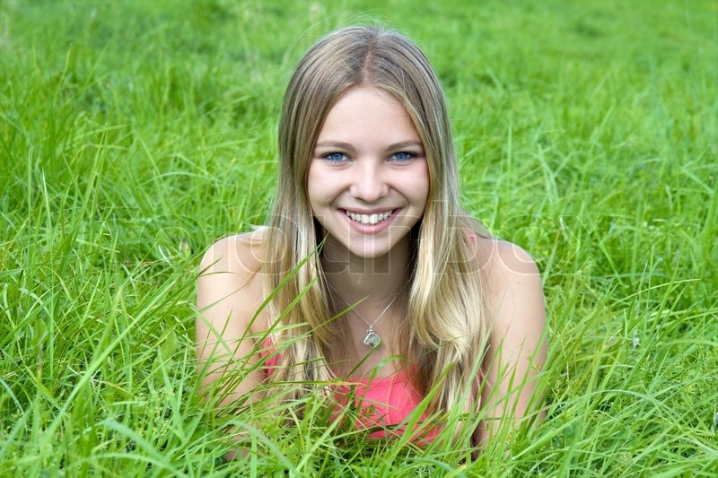 Beautiful girl lying on grass field stock photo colourbox for Pretty grass