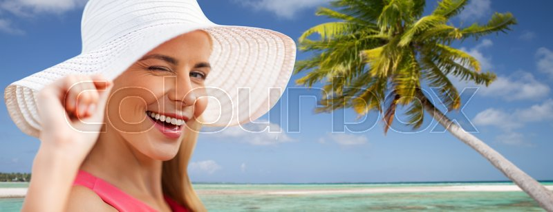 Summer, fashion and people concept - portrait of beautiful smiling woman in sun hat over tropical beach background in french polynesia, stock photo