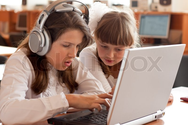 Stock image of 'Two schoolgirls performs task using notebook'