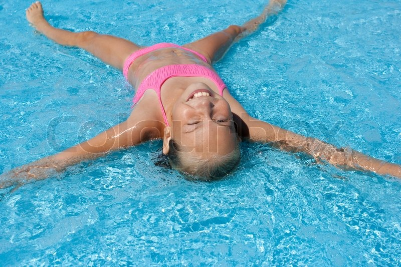 Happy Girl Lying On Her Back In Pool Stock Photo Colourbox
