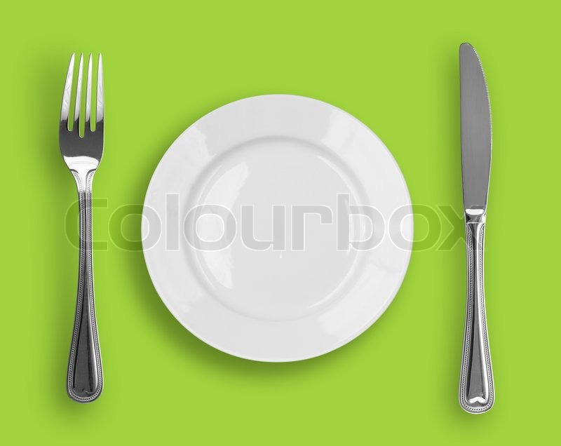 Knife White Plate And Fork On Green Background Stock