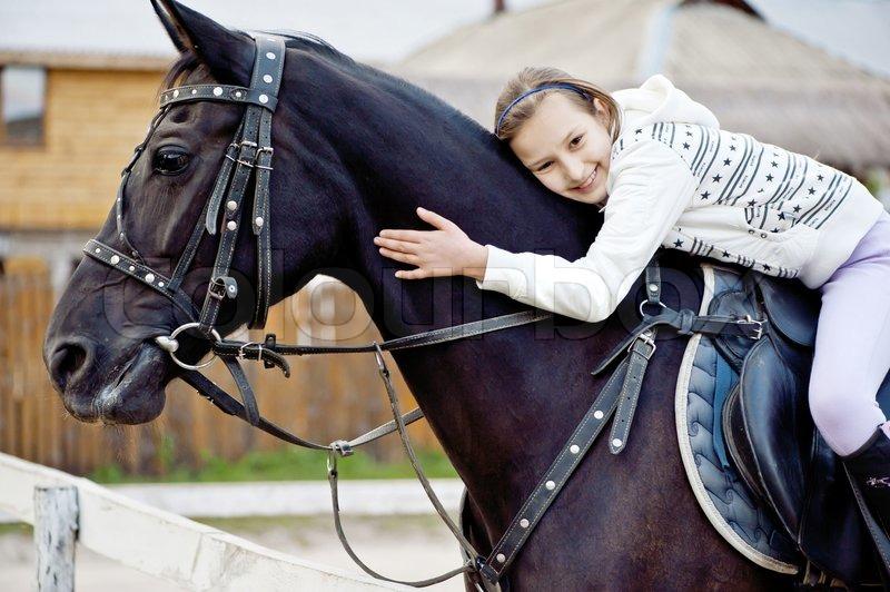 ein lächelndes mädchen auf einem schwarzen pferd umarmt