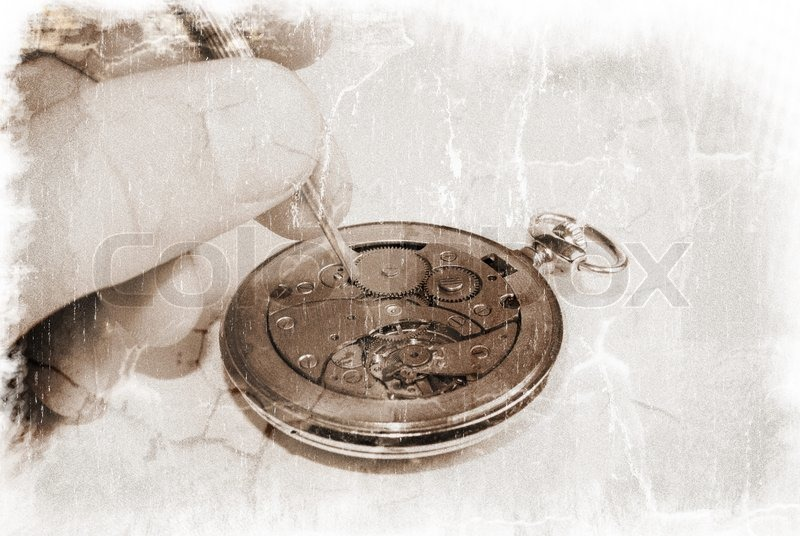 Hand holding a watch screwdriver and an old watch mechanism (vintage style), stock photo