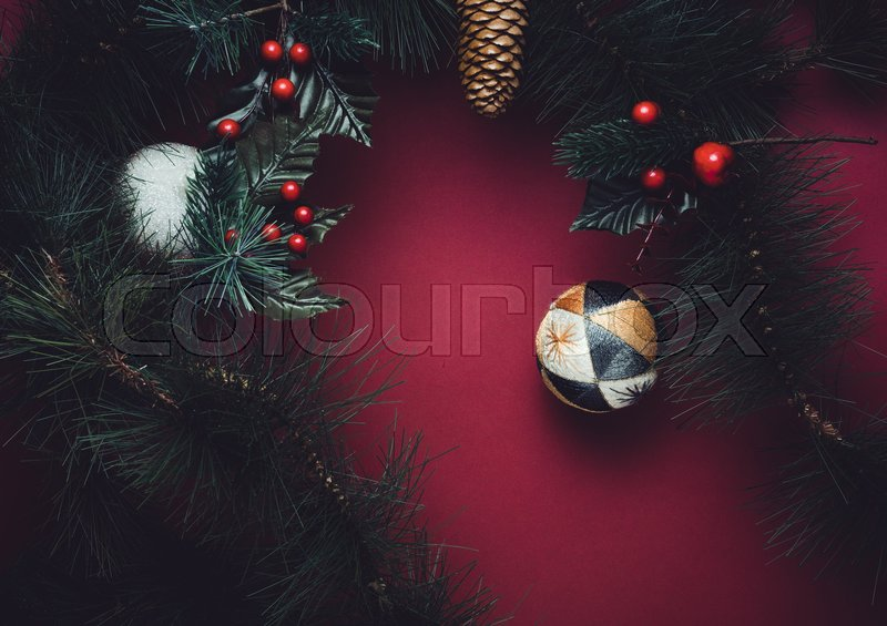 Christmas ball and fir branches for wreath with cherry and pine cone on red table background. winter holiday festive celebration concept, stock photo