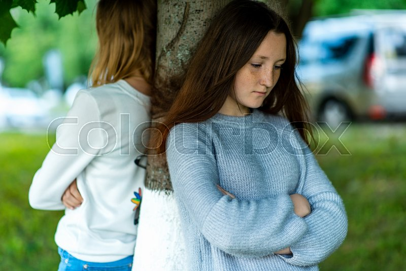 Two girlfriends in the summer in a park in nature. Offended each other. Friends quarreled. Negative among the girls. Problems in the relationship. Dissatisfaction with each other. Stand near a tree, stock photo
