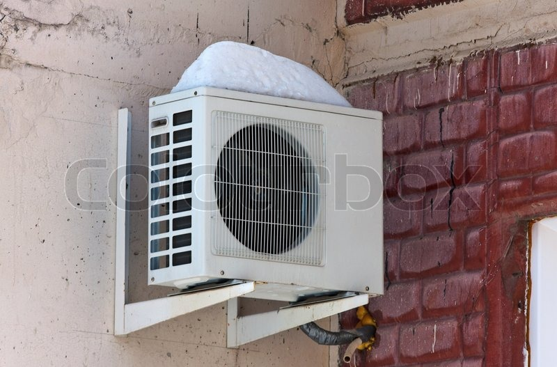 Air conditioning heat pump mounted on brick wall, stock photo