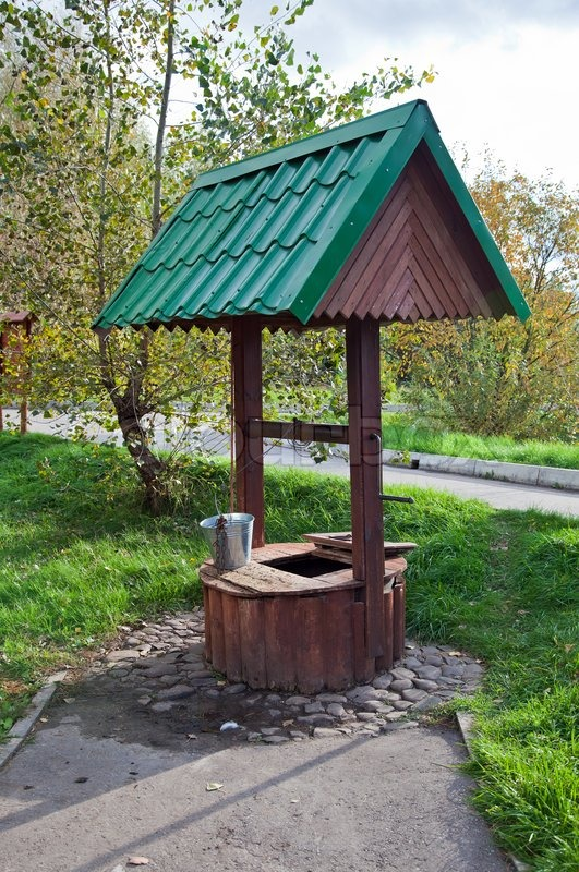 Stock image of 'Countryside water well with a bucket.'