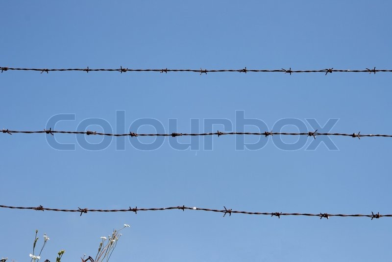 Three rusty strands of barbed wire over blue sky background, stock photo
