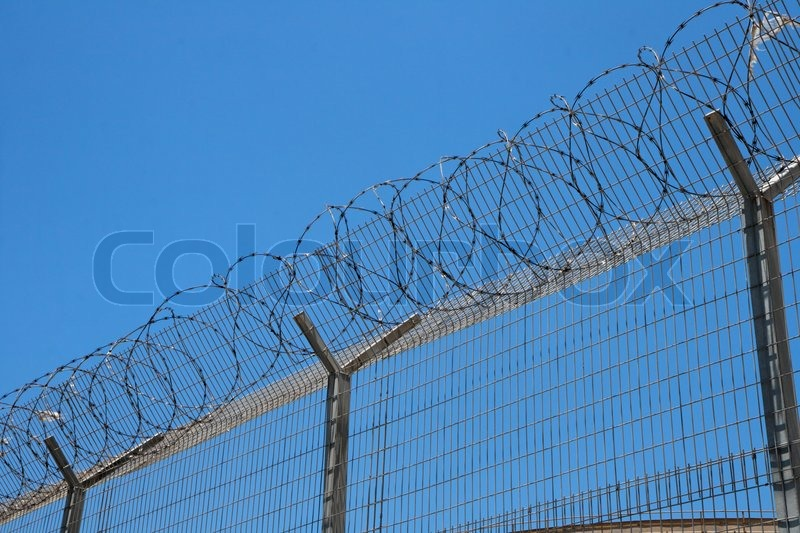 Fence with spiral barbed wire on top on sky background | Stock Photo ...