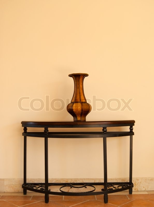 Stock image of 'Beautiful wooden vase on table near the wall'