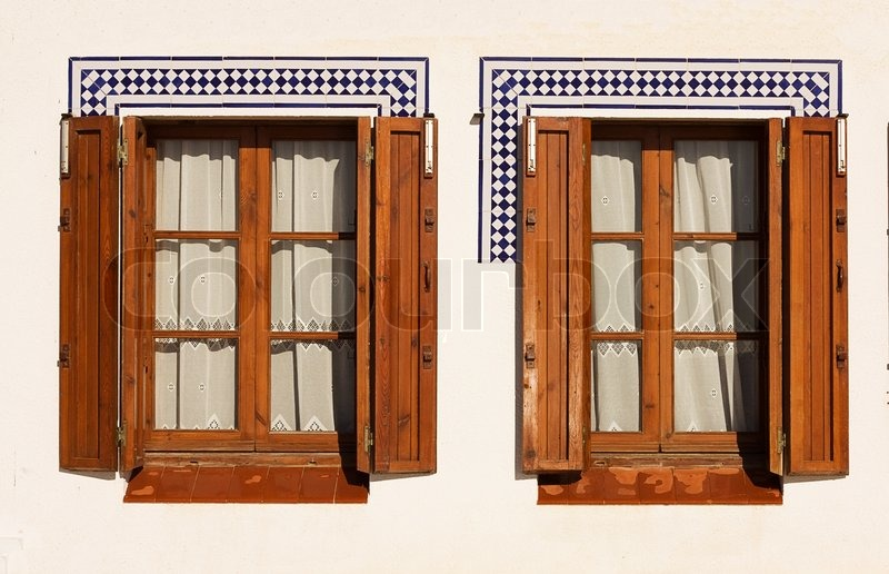 Windows with wooden shutters in the spanish coastal town for Spanish style window shutters