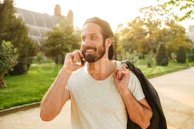 Portrait of muscular attractive guy wearing cap and white t-shirt holding leather jacket on shoulder and talking on cell phone ,during walk in green park, stock photo