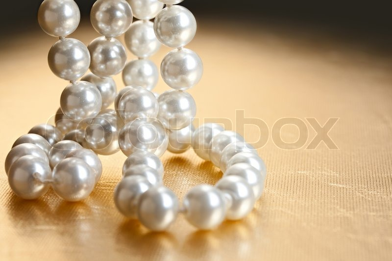 String of pearls on golden surface | Stock Photo