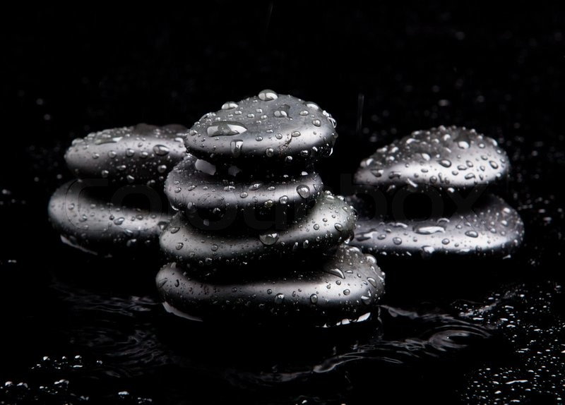 Black shiny zen stones with water drops over black background stock photo colourbox