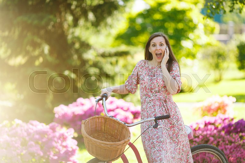 Portrait of trendy young woman in long pink floral dress stop to riding on vintage bike with basket for purchases on flowers background outdoors. Pretty female recreation time in spring or summer park, stock photo