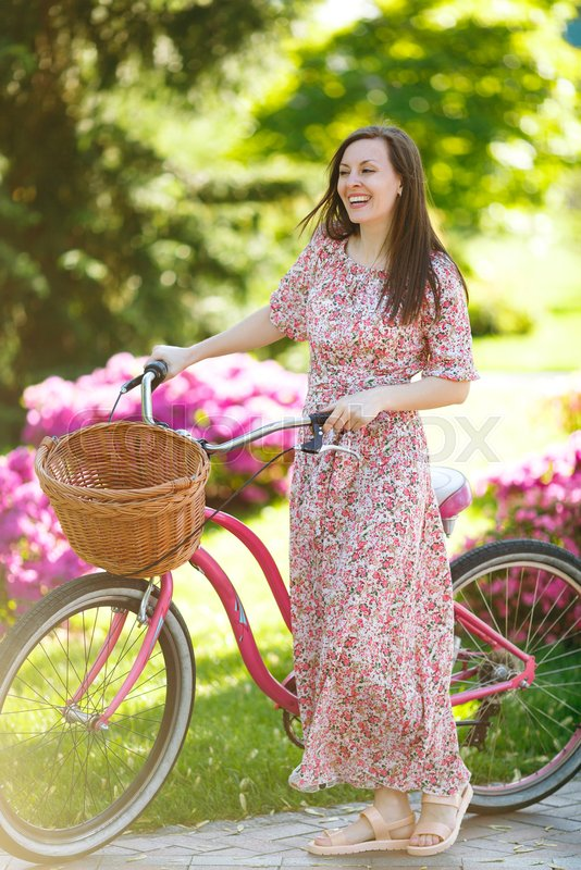 Portrait of smiling young woman in long pink floral dress stop to riding on vintage bike with basket for purchases on flowers background outdoors. Pretty female recreation time in spring, summer park, stock photo