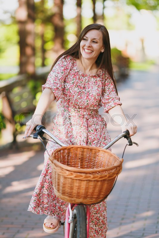 Portrait of trendy young woman in long pink floral dress riding on alley on vintage bike with basket for purchases, food or flowers outdoors, gorgeous female recreation time in spring or summer park, stock photo