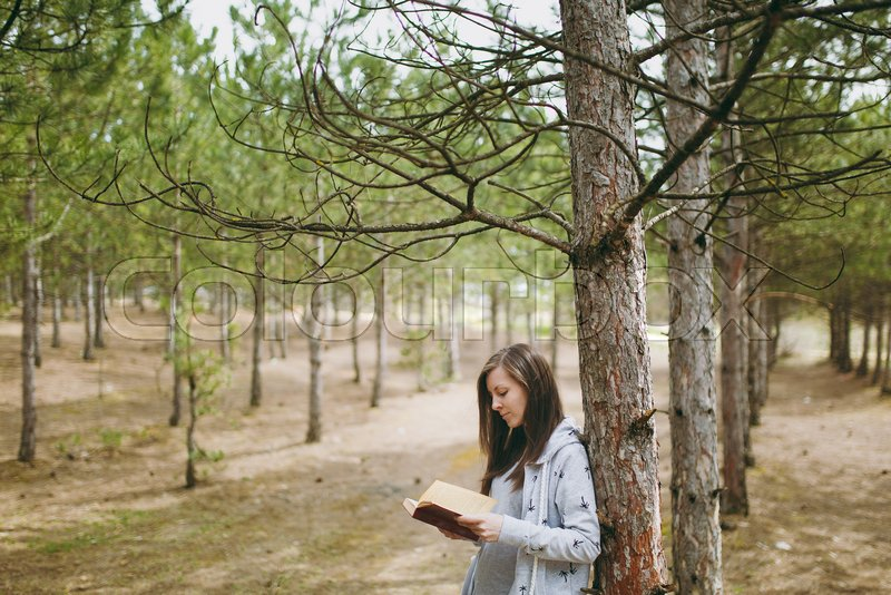Young calm beautiful woman in casual clothes leaning on tree studying reading book in big city park or forest on green blurred background. Student learning, education. Lifestyle, leisure concept, stock photo