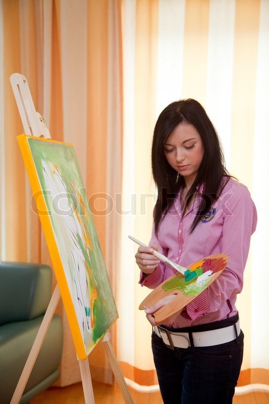 Young woman paints in her free time with oil paints on an ...