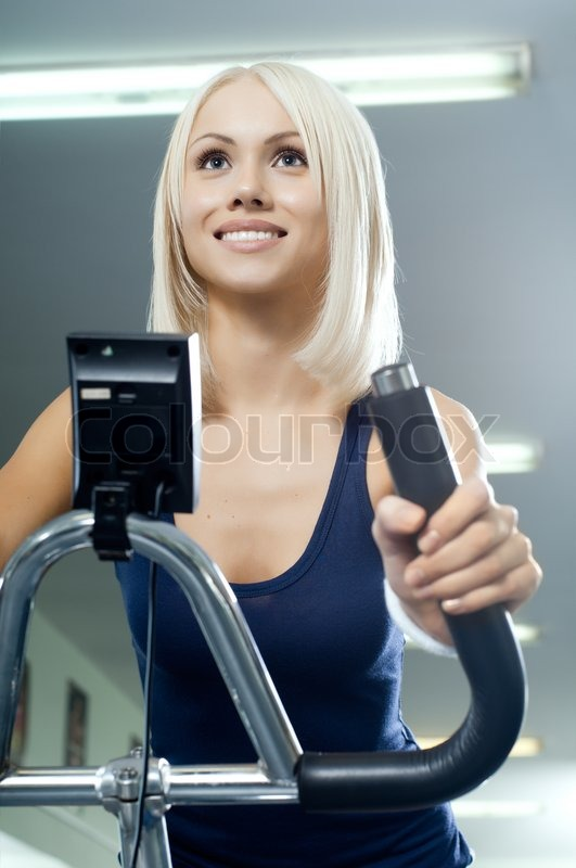 Happy cutie athletic girl , execute exercise on exercise bicycle and smile, in sport-hall, stock photo