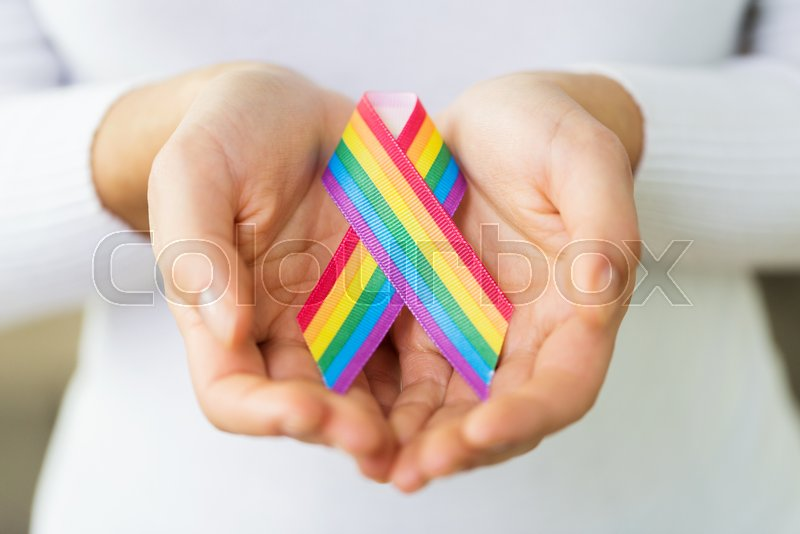 Homosexual and lgbt concept - close up of female hands holding gay pride awareness  ribbon | Stock Photo | Colourbox