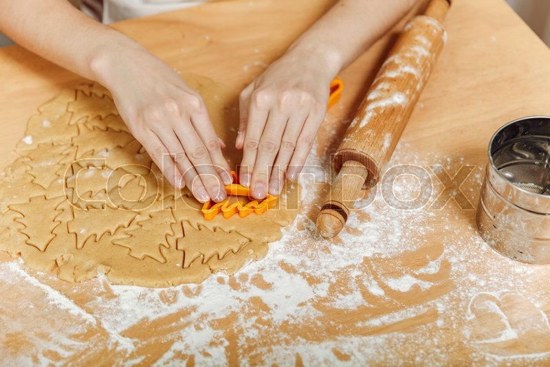 The European woman hands with healthy clean wich cook Christmas ginger biscuit in the kitchen. Happy mom 30-35 years roll out dough and cut out cookies at home, stock photo
