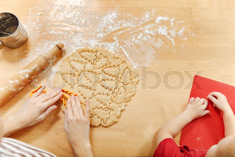 The hands of little kid boy who helps mother to cook Christmas ginger biscuit in light kitchen. Happy family mom and child roll out dough and cut out cookies at home. Top view, stock photo