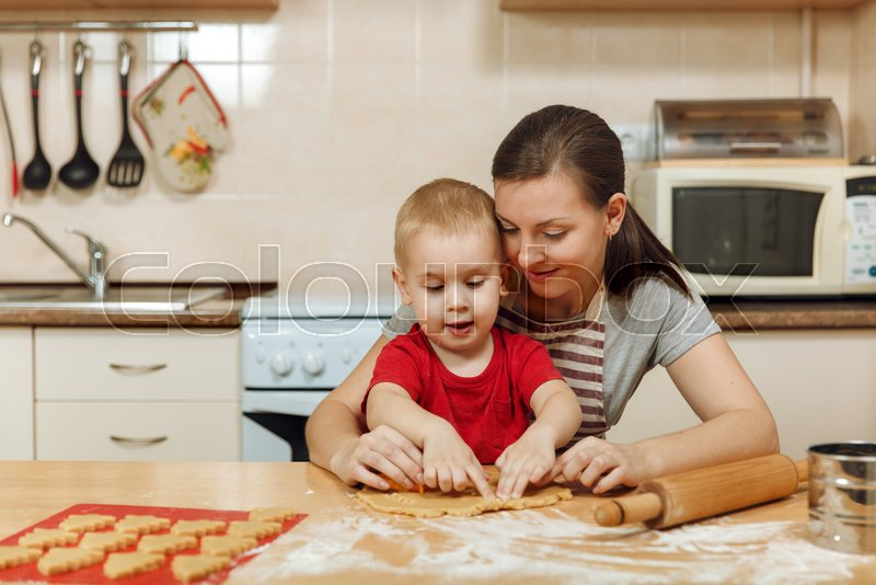 The little kid boy helps mother to cook Christmas ginger biscuit in light kitchen. Happy family mom 30-35 years and child 2-3 roll out dough and cut out cookies at home. Relationship and love concept, stock photo