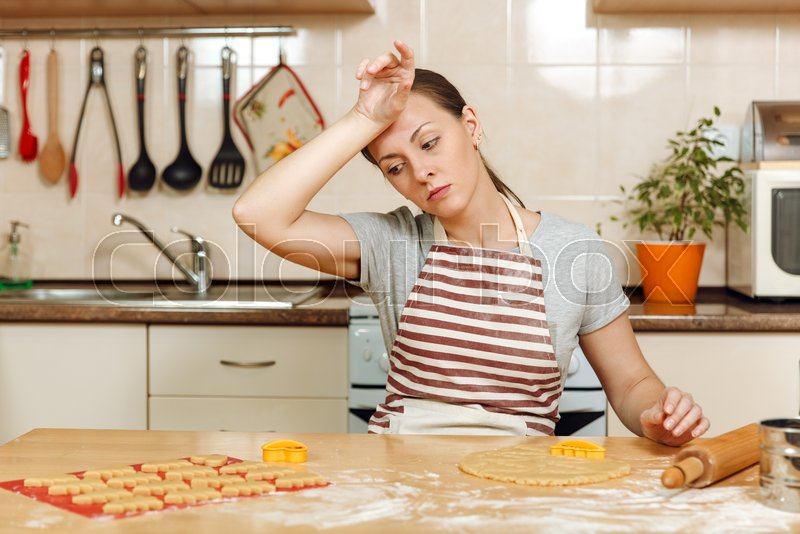 The young beautiful tired woman 30-35 years in apron sitting at a table with dough and rolling pin and going to prepare a Christmas ginger cakes in the light kitchen. Cooking home. Prepare food, stock photo