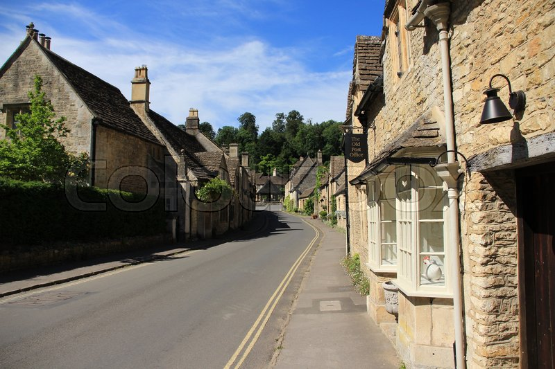 A bell and the old post office in one of the streets with terraced houses in the village Castle Combe in the Cotwolds in England on a sunny day in spring, stock photo