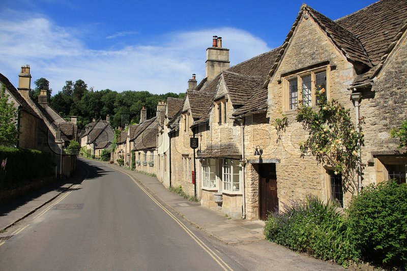 One of the streets with the old post office and terraced houses in the village Castle Combe in the Cotwolds in England on a sunny day in spring, stock photo