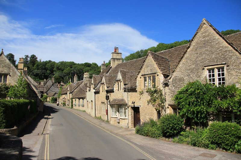 One of the streets with terraced houses in the village Castle Combe in the Cotwolds in England on a sunny day in spring, stock photo