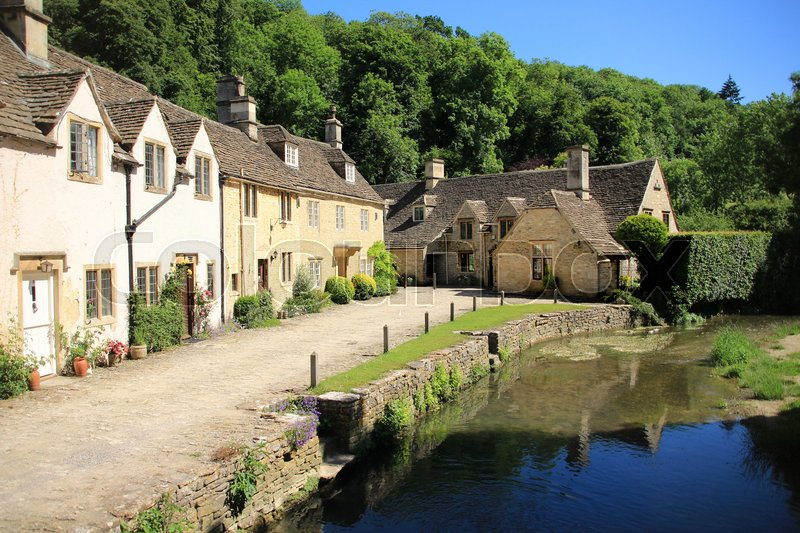 The river and one of the streets with terraced houses in the village Castle Combe in the Cotwolds in England on a sunny day in spring, stock photo