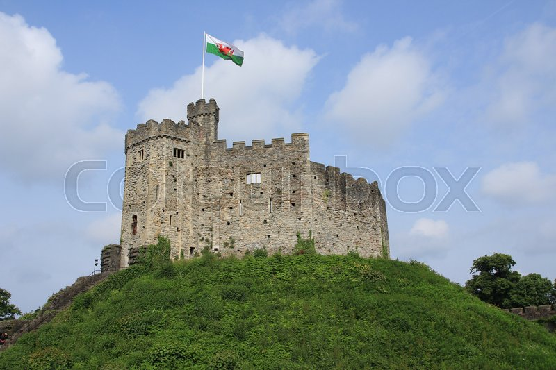 Blue sky with clouds, a waving flag and on the hill Cardiff Castle in the city Cardiff in Wales in spring, stock photo