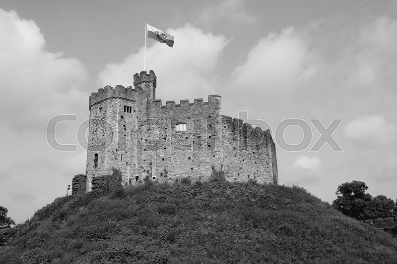 Clouds in the sky, waving flag and on the hill Cardiff Castle in the city Cardiff in Wales in black and white, stock photo