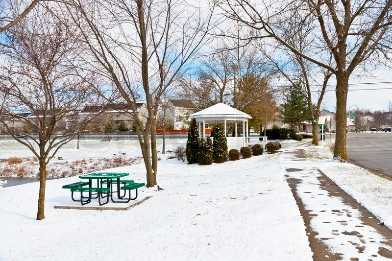 Winter city scene with a picnic table and gazebo at neighborhood recreation area, stock photo