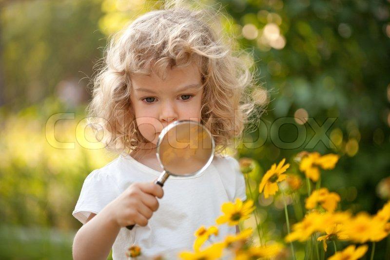 Cute child explorer flowers in garden stock photo colourbox