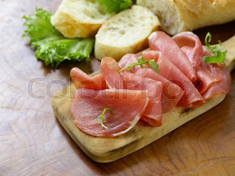Stock image of 'Smoked ham of pork on a wooden board'