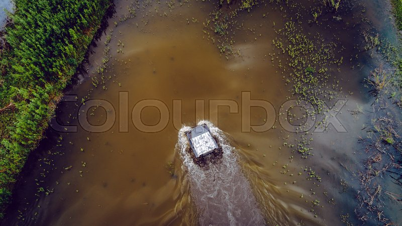 An off-road vehicle on leaves the river. The cross-country vehicle on the crosses the river. aerial drone view top above, stock photo