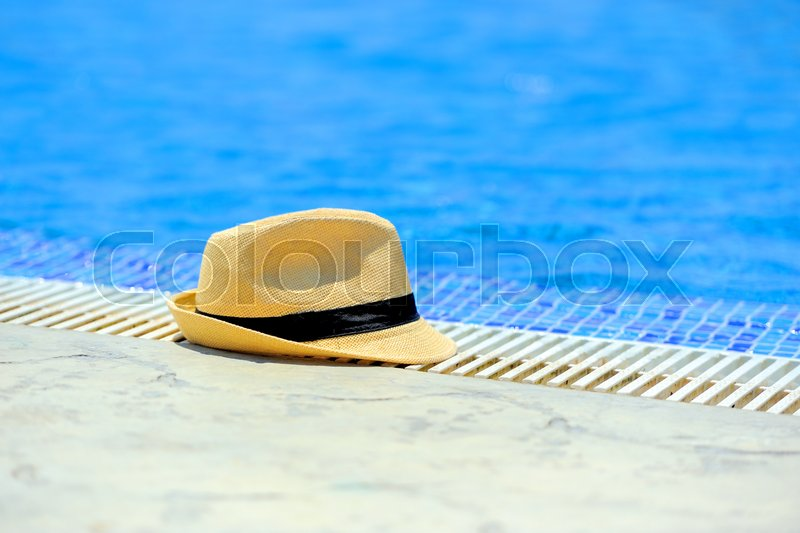 Yellow sun hat on the edge of the pool, stock photo