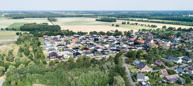 Typical German new housing development in the flat countryside of northern Germany between a forest and fields and meadows, made with drone, stock photo