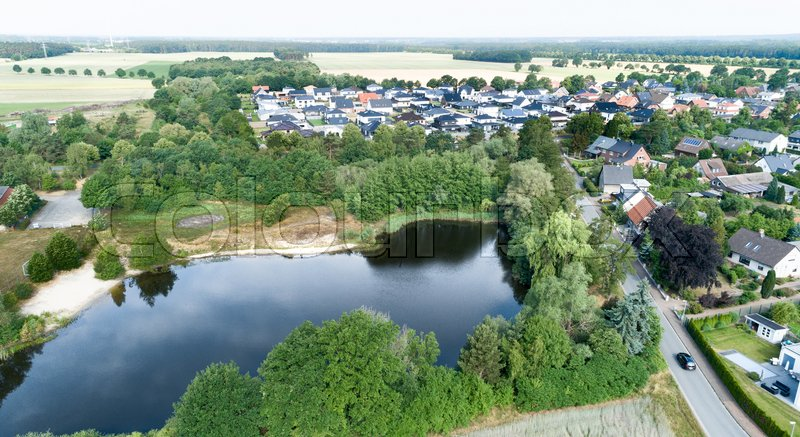 Aerial view of a suburb behind a small lake and a wooded area, with detached houses, semi-detached houses and terraced houses with small front gardens and green lawns in northern Germany, stock photo